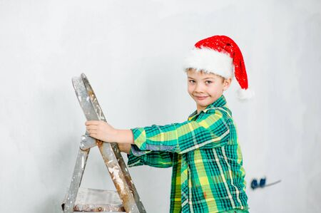 boy in a red christmas hat on a ladder.