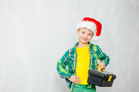 Young boy in red christmas  hat with toolbox. Space for text. Фото со стока