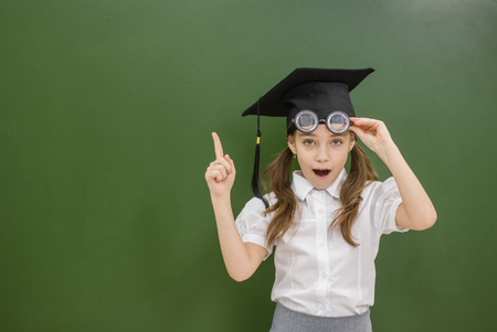 Shocked girl in graduation hat pointing away on empty chalkboard. Stock Photo
