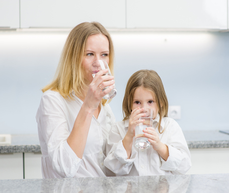 Little girl and woman drink water in the kitchen.