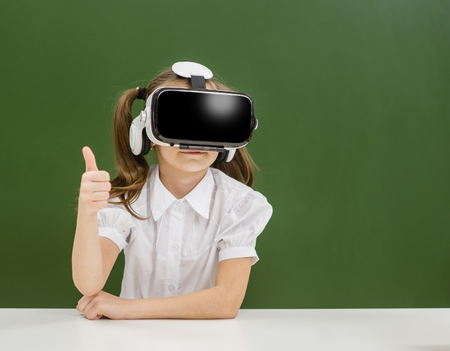 girl wearing VR headset and showing thumbs up on the background of a school board. Space for text. Stock Photo
