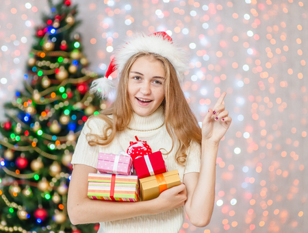 Happy young woman holding many present boxes and pointing away. Space for text. Stock Photo