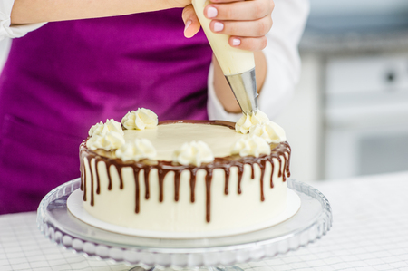 Close up woman`s hand decorating chocolate cake in the kitchen. Stock Photo