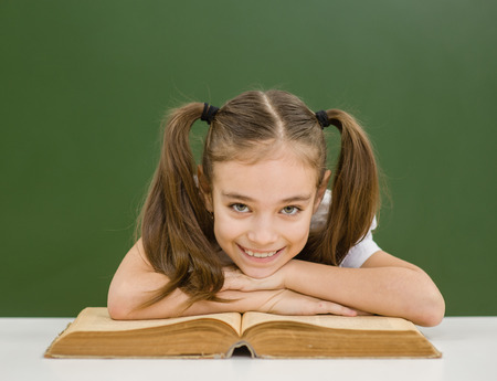 Happy girl studying and reading book at school.
