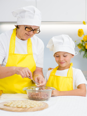 Happy grandmother teaches her grandson to make a dumplings.