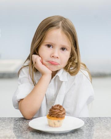sad girl with cupcake looking at camera. Stock Photo