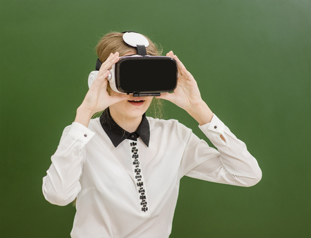 Teen  girl wearing VR headset on a green background. Stock Photo