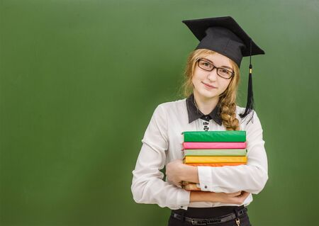 Teen girl in graduation cap with books standing near green chalkboard. Space for text. Stock Photo