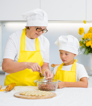 grandmother teaches her grandson to make a dumplings.