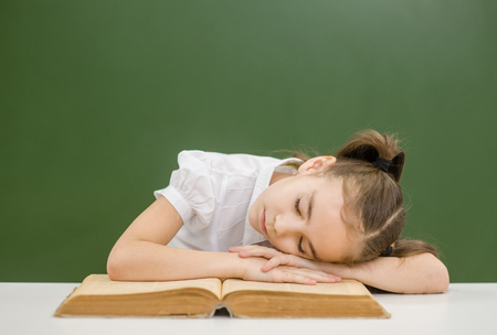 Tired girl sleeping on the book in classroom. Space for text.
