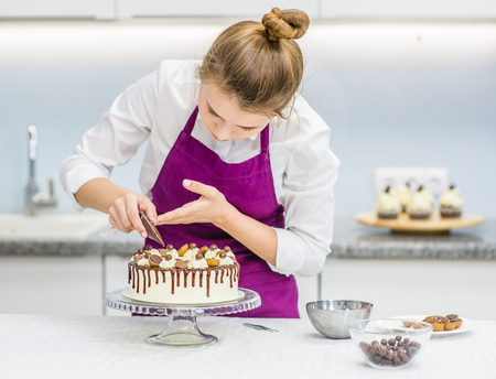 woman decorating chocolate cake in the kitchen.