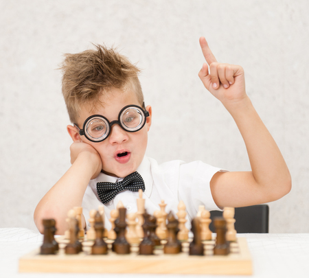 nerd boy sits at the chessboard and shows finger up. Idea concept. Stock Photo