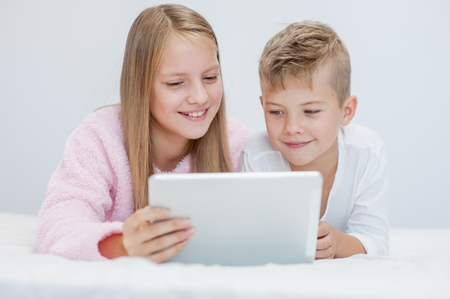 Smiling kids with tablet computer on the bed.