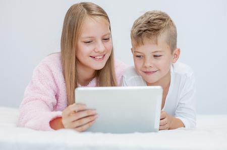 Glimlachende kinderen met tabletcomputer op het bed.