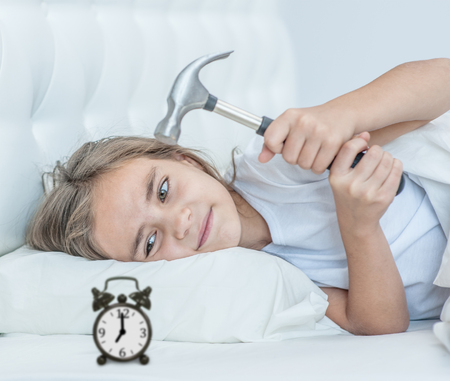 Lazy and angry girl splits alarm clock with hammer.