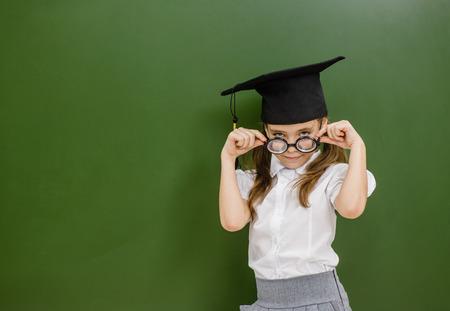 nerd girl in graduation hat near empty chalkboard.