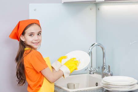 happy girl washes dishes at the kitchen sink in the kitchen. Banco de Imagens