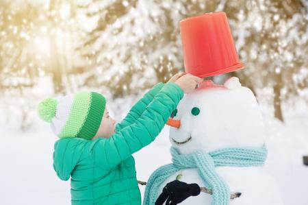 Kleiner Junge stellt dem Schneemann einen Eimer auf den Kopf. Standard-Bild - 100314484