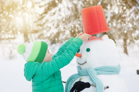 Little boy puts a bucket on the snowman's head. Banque d'images