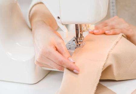 Dressmaker hand using sewing machine. Stock Photo