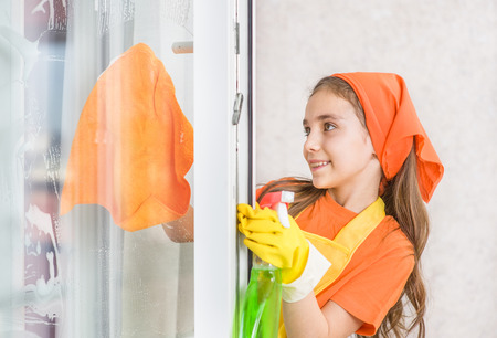 Happy girl doing housework, washes windows.