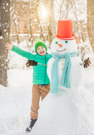 Joyful boy with snowman at sunset. Stok Fotoğraf