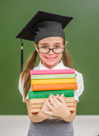 Happy little girl in graduation cap standing with book near a school board.