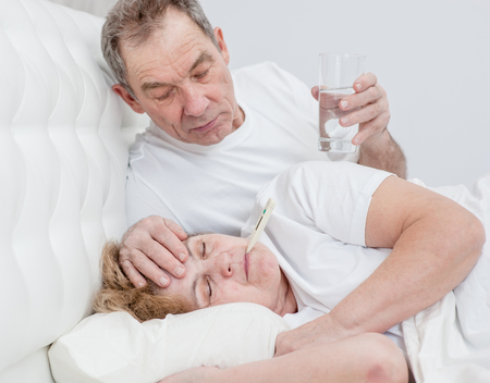 an elderly man with glass of the water touches forehead his wife, checking the temperature.