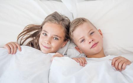 jongen en meisje liggen onder een deken hun haar aan te raken. Stockfoto