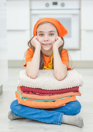 Little girl with washed and dried clothes sitting on the floor.