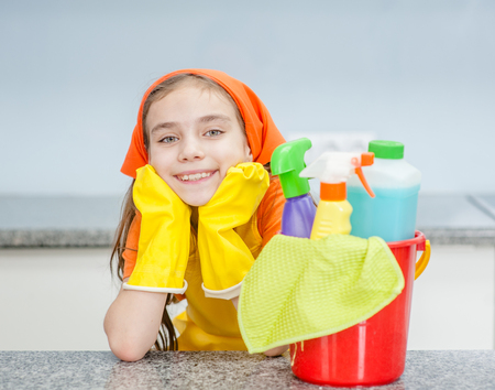 Happy little girl with cleaning supplies in bucket at kitchen.