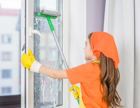 Happy girl washes the window with a scraper. Stock Photo