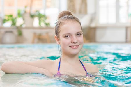 Smiling beautiful teen girl in the pool.