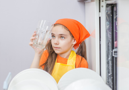 Little girl in apron  looking at clean glass crouching near dish washer. Stock Photo