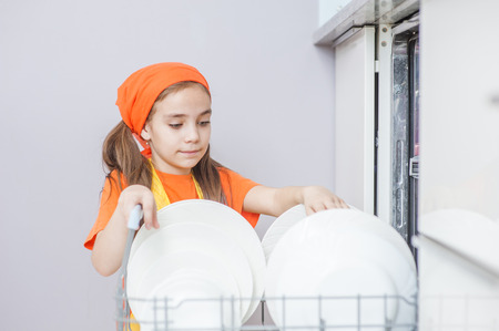 girl puts dishes in the dishwasher. Banque d'images