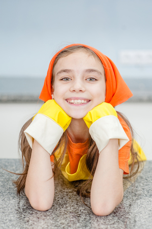 little girl in rubber gloves in the kitchen.