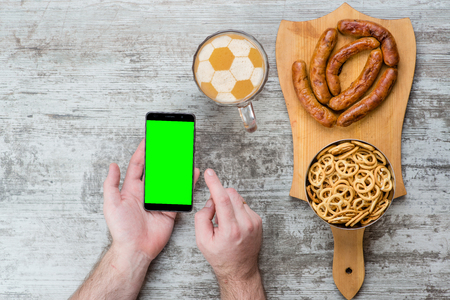 Male hand holding smartphone mobile cell phone near beer with a soccer ball on a beer foam and snacks, food delivery order app application concept.