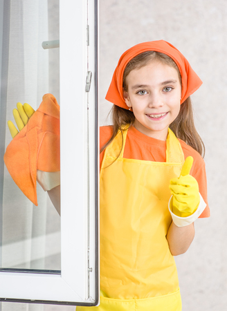 Smiling little girl cleaning window with rag and showing thumbs up.