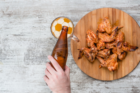 a man's hand pours beer from a bottle into a mug with a soccer ball on a beer foam near fried chicken wings. Top view.
