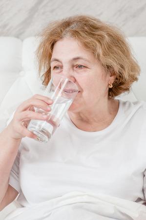 senior woman  drinks water before bedtime.