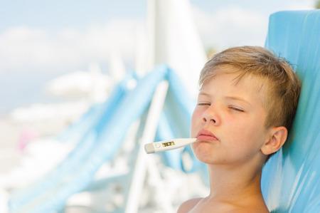 Mały chłopiec na gorącej plaży po udarze słonecznym mierzy temperaturę. Miejsce na tekst. Zdjęcie Seryjne