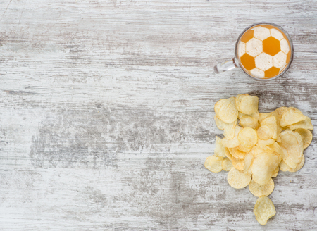 mug of beer with a soccer ball on a beer foam with chips.  Top view. Space for text. Banque d'images