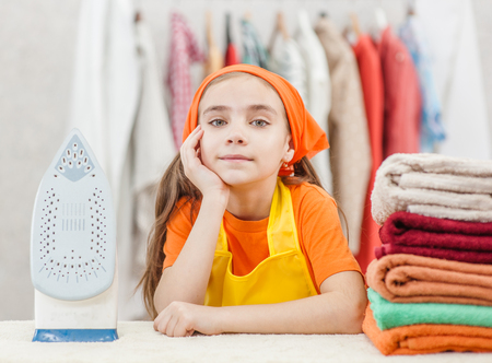 Smiling little girl is leaning on ironing board, looking at camera and smiling while ironing clothes at home. Banque d'images