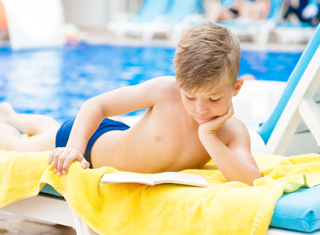 Little boy is reading a book by the pool.  Relaxation resting vacations concept.