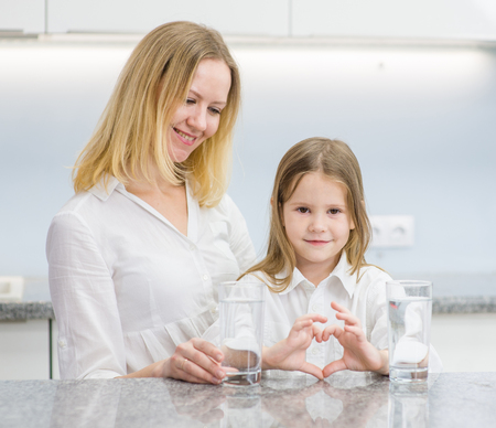 happy mother and little girl shows a heart sign at kitchen. Stock Photo