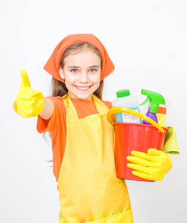 Happy girl with cleaning supplies in bucket standing on white background and showing thumbs up.