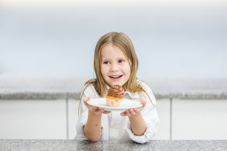 Happy little girl with cupcake on the table.