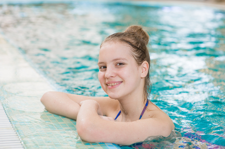 Smiling beautiful teen girl in the pool.