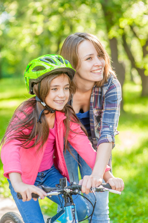 mom teaches her daughter to ride a bicycle in the park.