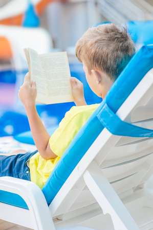 Little boy reading a book by the pool.  Relaxation resting vacations concept.